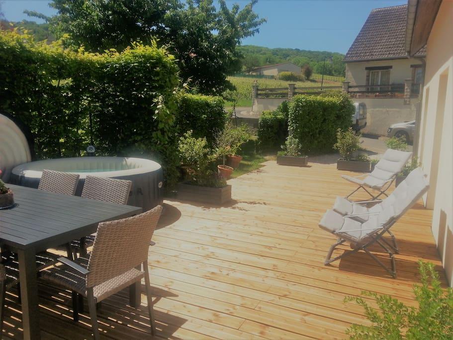 Vaste terrasse en bois en bordure du jardin.