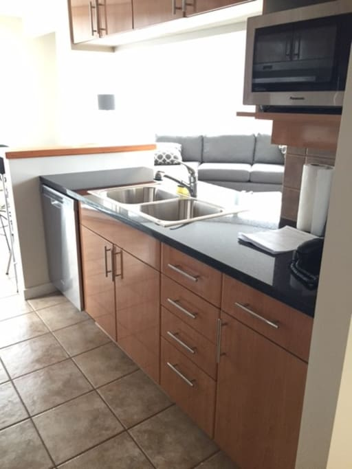 Open kitchen with stainless appliances and microwave.
