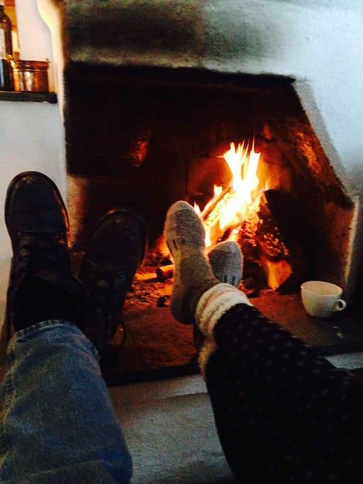 Warm your feet by split birch wood indoor fire.