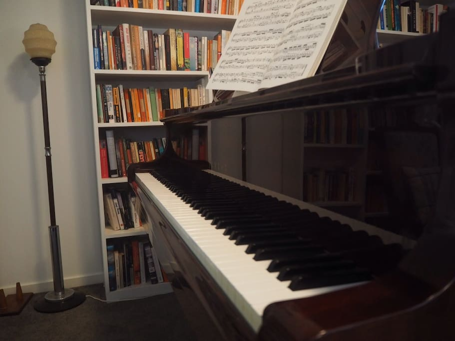 Baby grand piano, bookshelves and Bach
