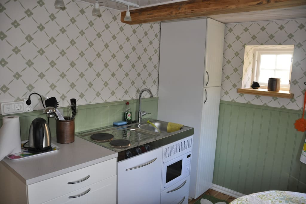 Small kitchen with refrigerator, stove, microwave