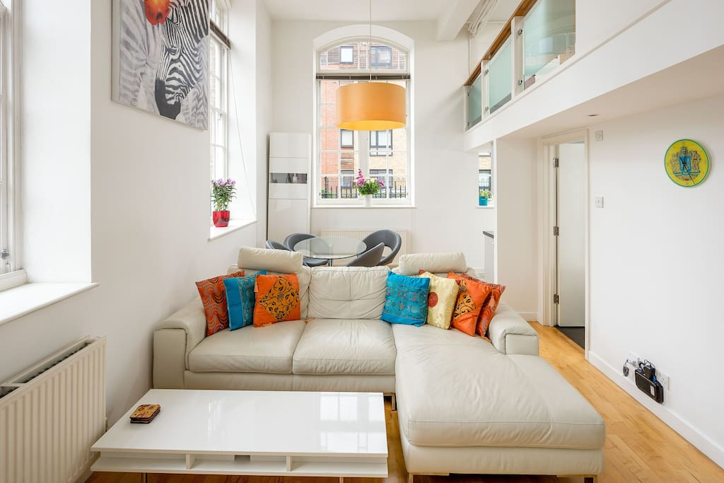 The stylish living area is light and airy with high ceilings and a mezzanine level.