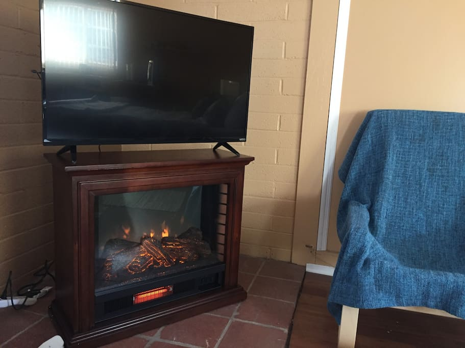 Indoor fireplace and television. The fireplace is a heater (no actual fire).