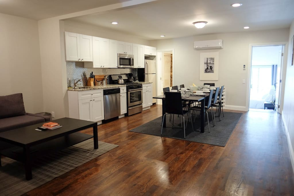 Newly renovated living room and kitchen with stainless steel appliances.