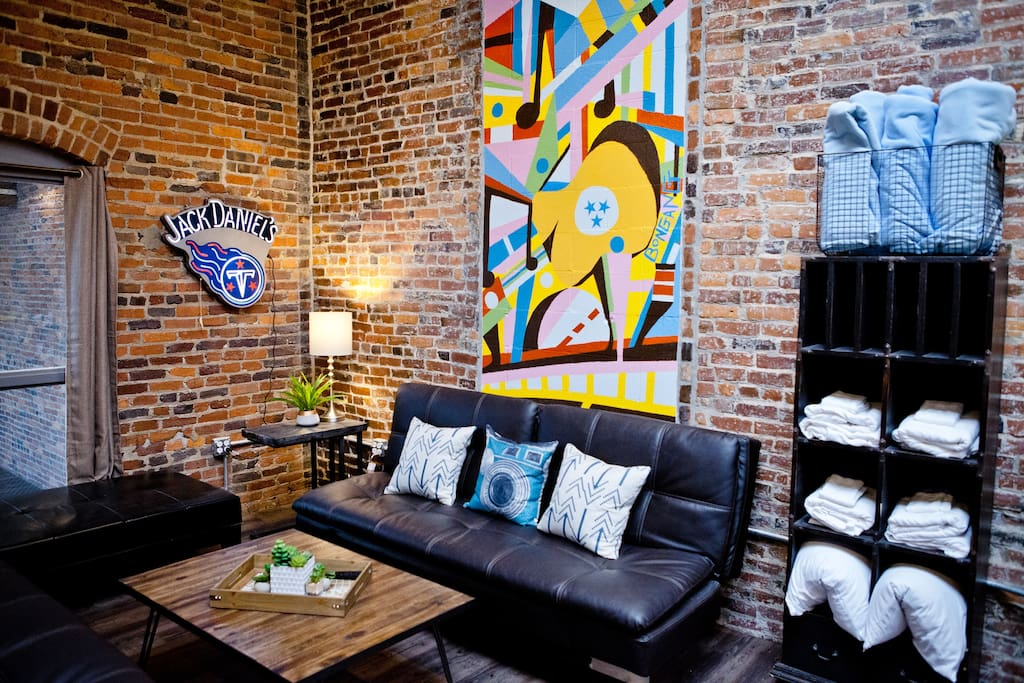 """Our new group rental has TONS of space and custom artwork! Enjoy 4 dorm-style bedrooms, 3 showers, 3 toilets, 70"""" TV, Kitchenette, HUGE custom table, and lots of Lounge Space."""