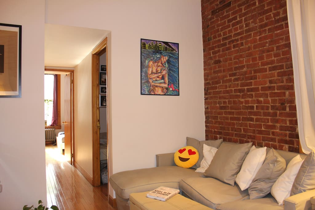 Upper East Side charm: exposed brick, high ceilings, immaculate hardwood floors. View of living room from middle of apartment. Bedrooms down hall.