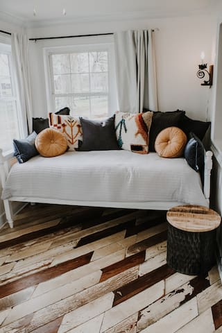 The sun porch foyer has a twin sized daybed and reading chair. The room is complete with blackout curtains and reclaimed wood floor.