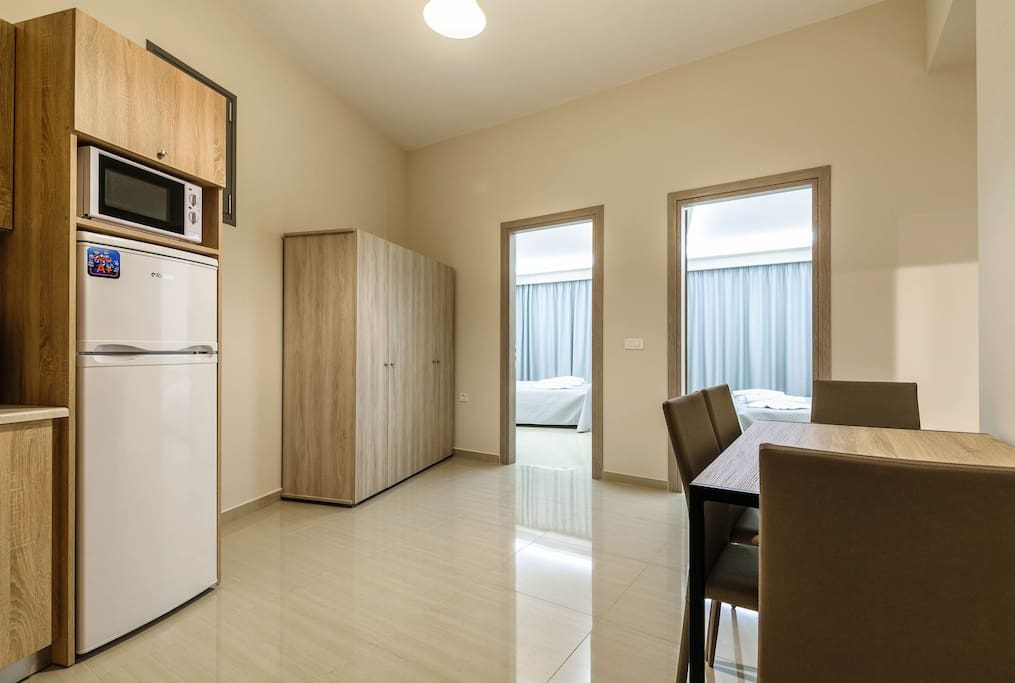 Fully equipped kitchenette with all necessary kitchenware, cutlery, fridge, cooking rings, electric kettle, toaster, microwave, coffee machine and a dining table for 4 people.