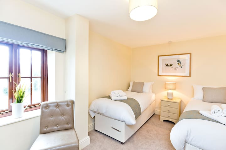 Upstairs second bedroom with zip & link beds that can be made into Double or Twin with views over the courtyard . Towels provided, tastefully decorated with a double wardrobe, chest of drawers and bedside cabinet.