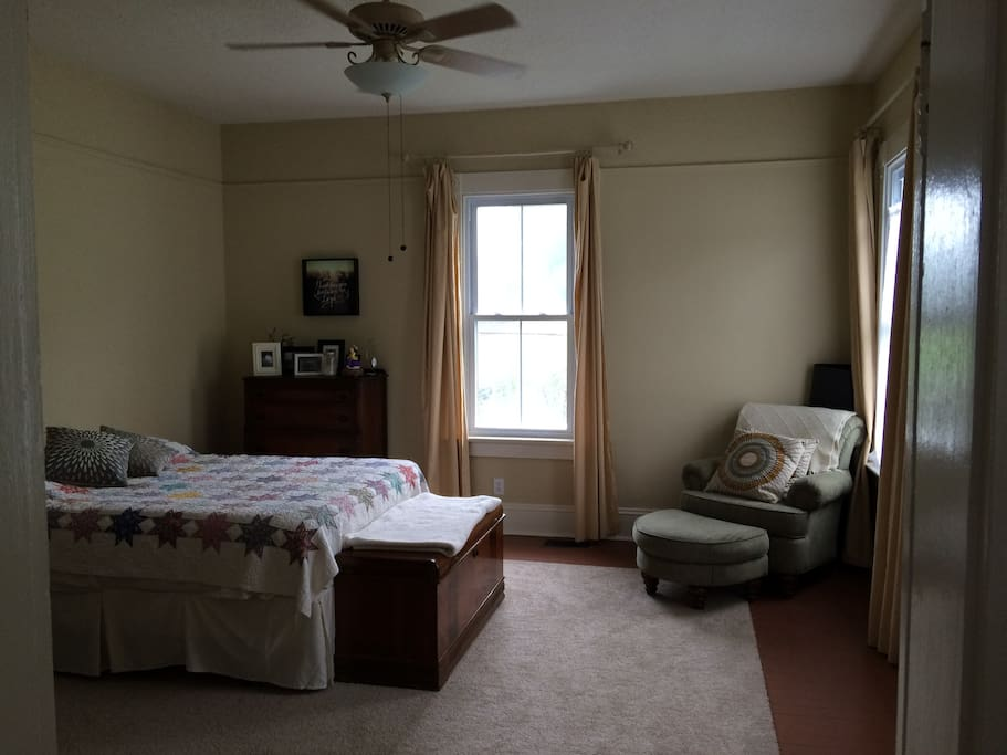 Large bedroom with sitting area and queen-size bed. Downstairs.