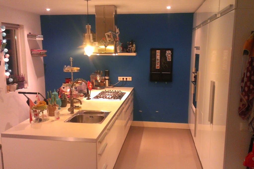 Modern big kitchen with  a.o. a dishwasher, an oven, sink, microwave, stove.
