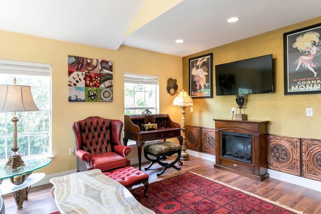 Electric fireplace for ambiance, baroque Steampunk style tile on a metallic accent wall with dimmer recess lighting.  19th century writing desk overlooking a greenbelt provides a great space for work or media