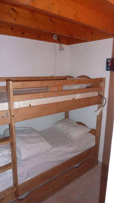 La chambre du bas est composée de 2 lits superposés avec 1 lit gigogne