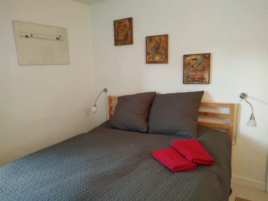 Sengen med sengelamper og hyggelige billeder