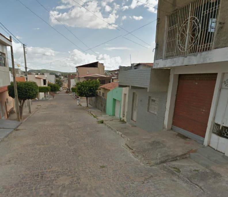 Visão da rua e o duplex a direita. Fachada rústica do duplex a direita.
