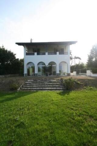 Dans villa neo-basque, veranda en arcades sur jardin.Parking privé à droite maison.