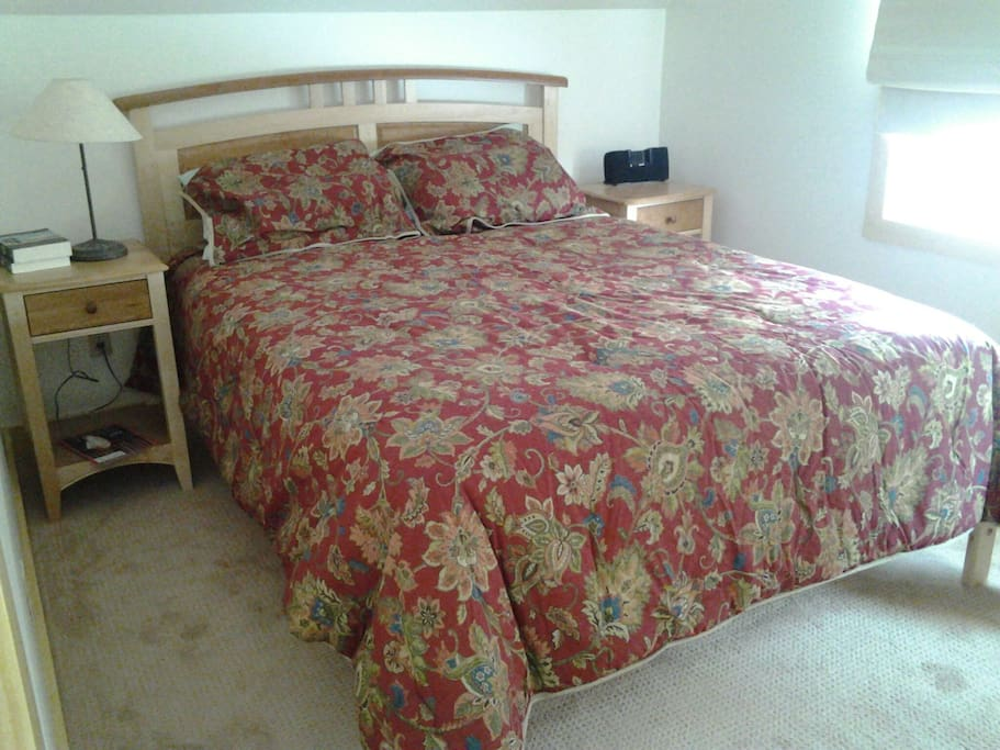 Bedroom with queen memory foam mattress, carpeted floor and ceiling fan.