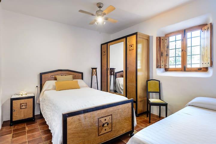 dormitorio en planta baja con 2 camas individuales.  ventilador de techo.