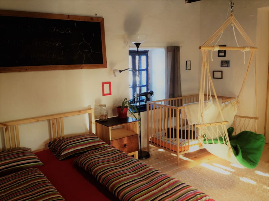 Your room with a double bed and a simple bed, a little bed for children, two hammock chairs and sunshine.