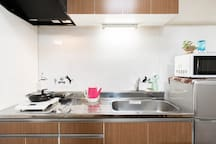 Kitchen with induction cooker, refrigerator, microwave, kettle, and dining table for light cooking.