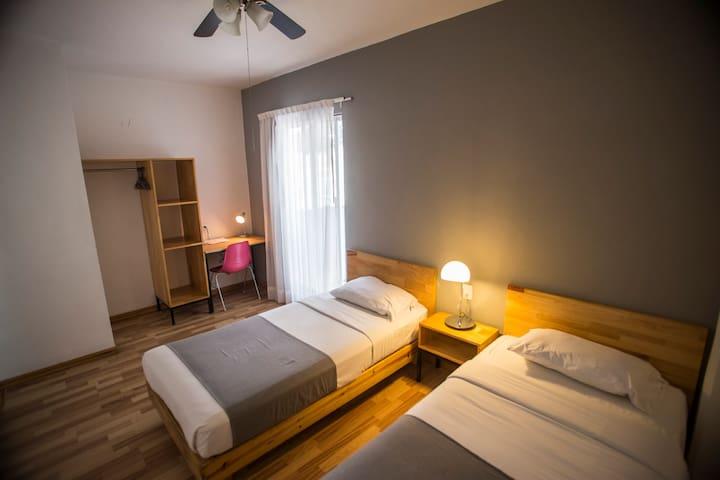 Habitación privada Hostal Doble con 2 camas individuales para 2 personas, regadera y lavabo DENTRO de la habitación, TV con cable, aire acondicionado, ventilador, closet, escritorio, y cortinas black out. W/C es compartido.