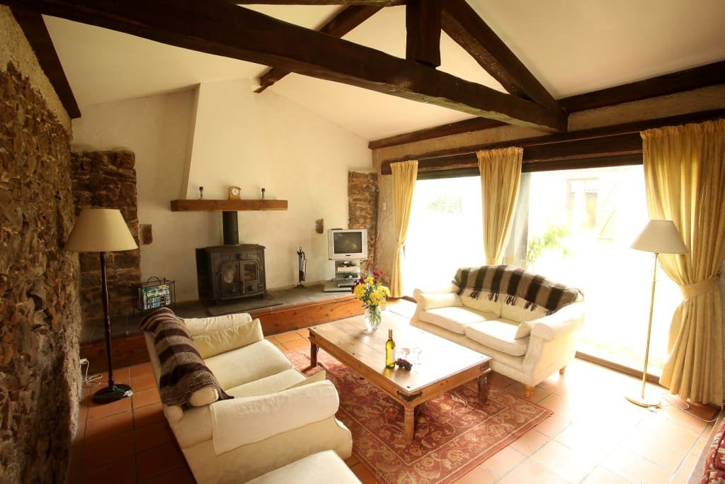 Living room with large feature fireplace, plenty of comfortable seating and a TV with french and english channels.