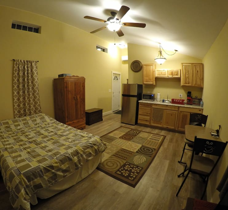 Panoramic view of unit shows the open floor plan, high ceilings, and ample lighting.