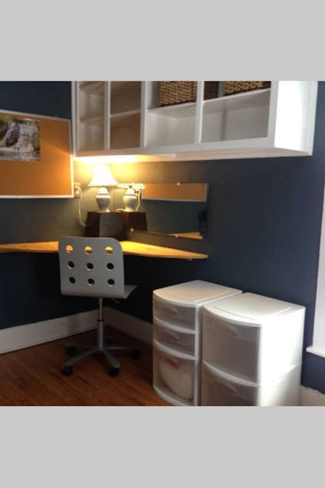 Corner desk space with lots of storage in shelves and drawers.