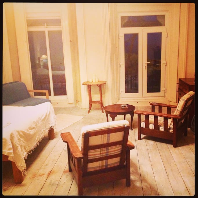 Here's the main room with bed, basic furniture and french windows leading to the seafront balcony and shutters for the windows