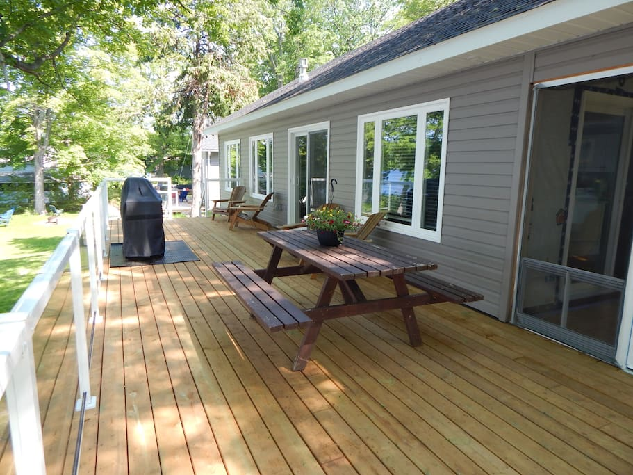 Deck with a picnic table, patio chairs, and glass paneled railings for an unobstructed view of the lake