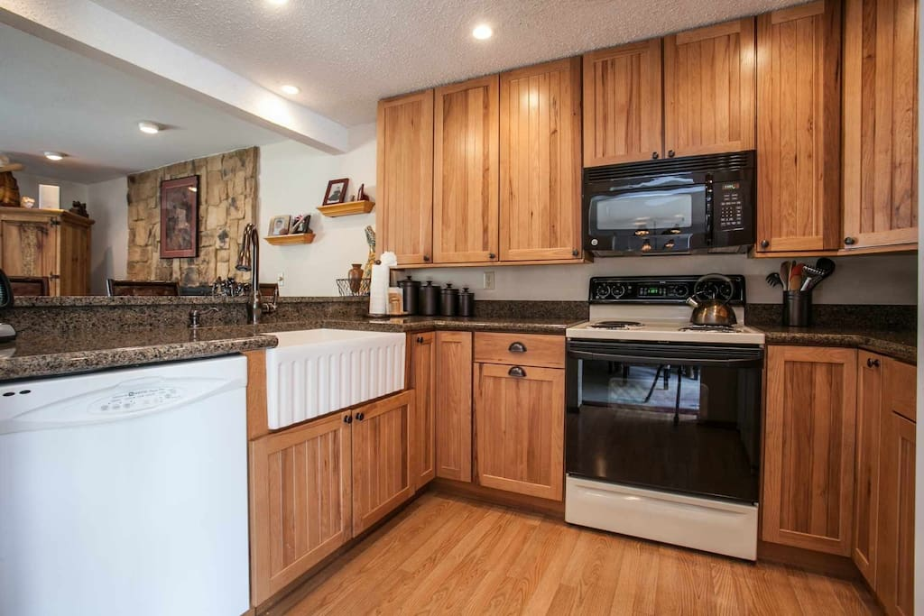 Fully equipped kitchen with granite counter tops, looks out to living room.