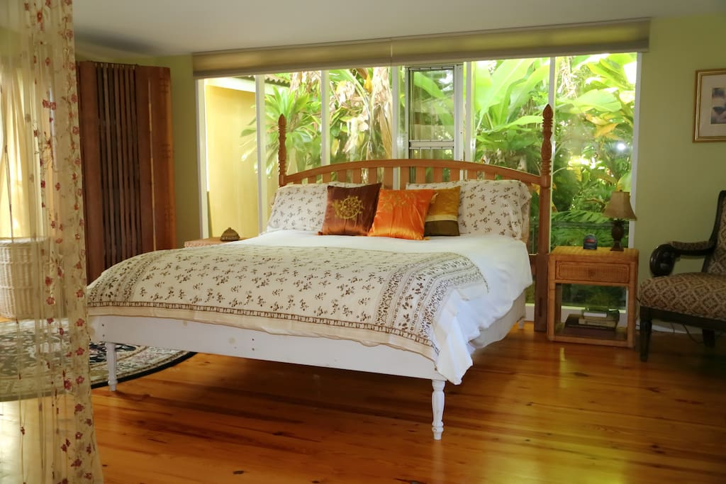 King size bed with luxurious sheets and comfortor dreamy garden view surrounded by the green lush landscape.