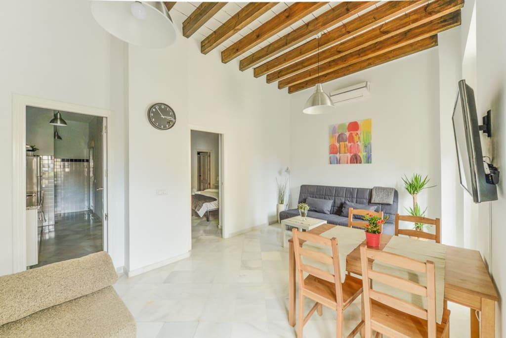 Salón, cocina a la izquierda y dormitorio interior a la derecha