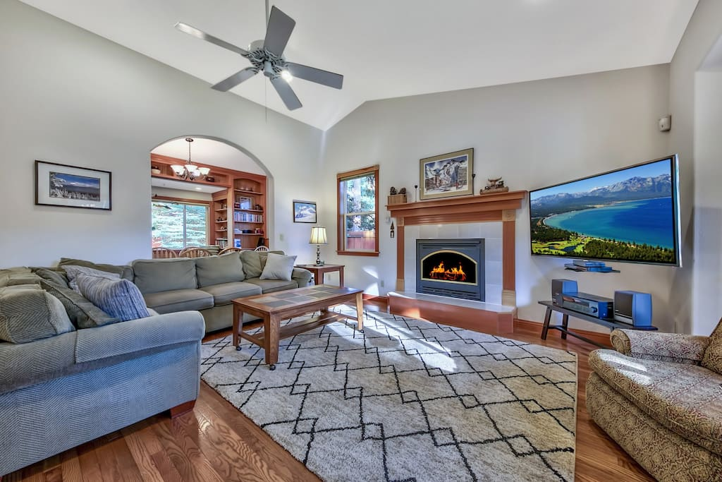 Spread out on the L-shaped couch next to the gas fireplace in the living area.