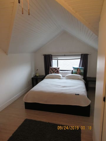 Private bedroom with queen size bed of suite 5 with vaulted ceilings, large closet with hangbar and a separate shelving unit as well as a chest of drawers.