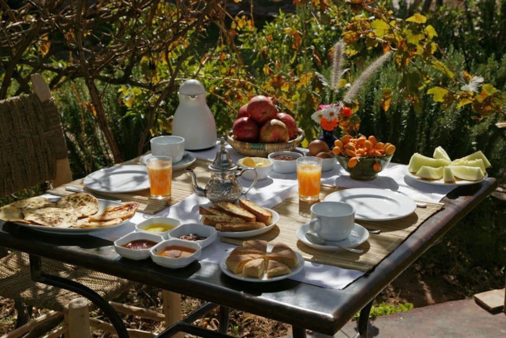 Table du petit dejeuner avec fruit jus de fruit yaourt maison, crépes et pains marocains confitures maison café thé chocolat....