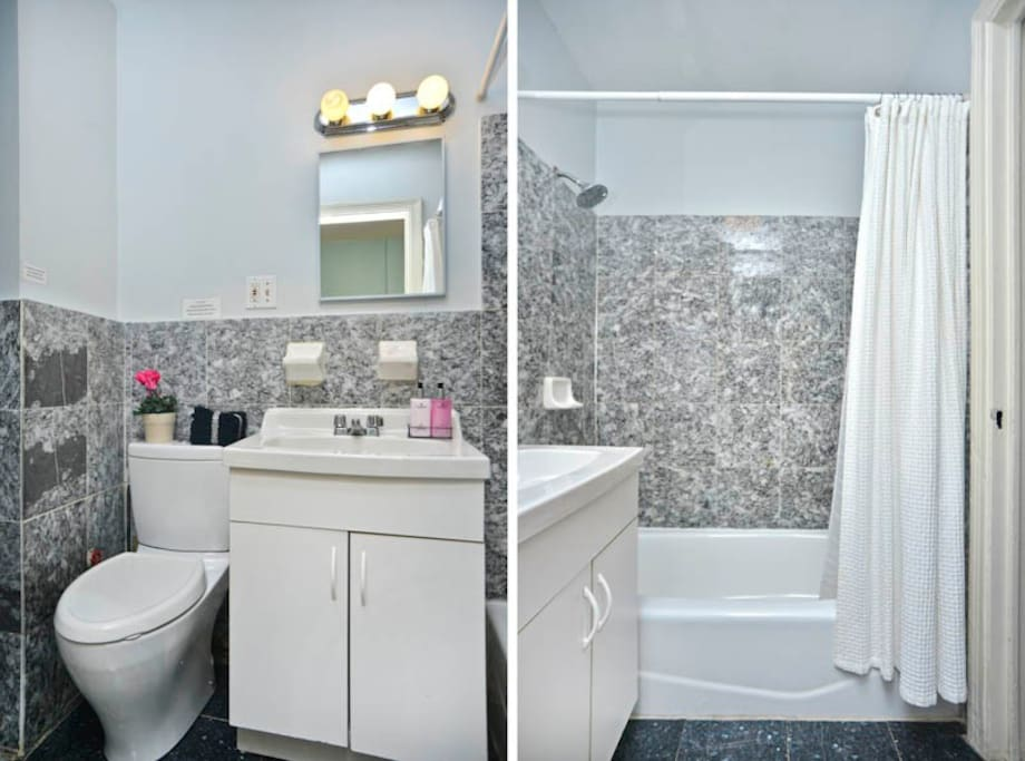 Bathroom features white cabinetry and exquisite tiling throughout