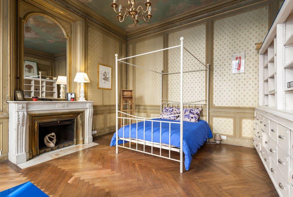 Le lit a baldaquin dans une chambre aux boiseries et papier peint d'époque .