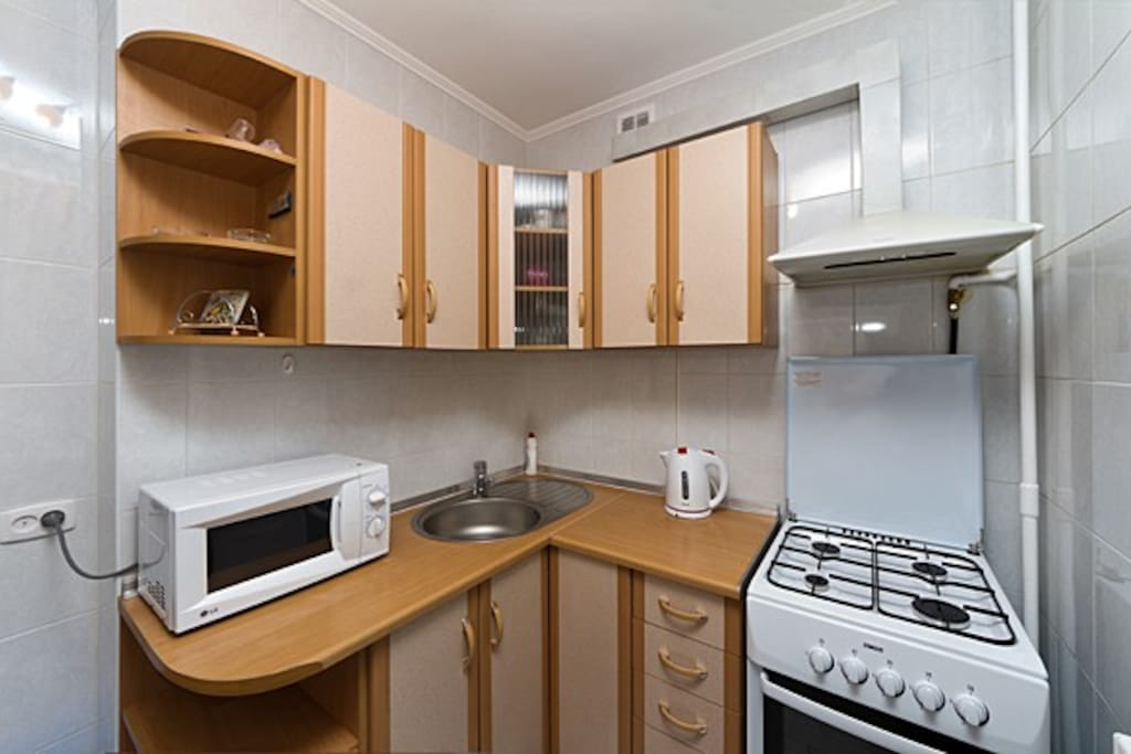 Modern kitchen with refrigerator with freezer, gas stove, gas oven, microwave, electric kettle and kitchen utensils. There is dining table.