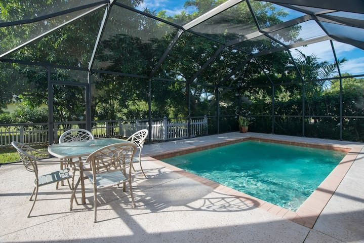 Private heated pool in enclosed lanai with patio furniture and lounge chairs