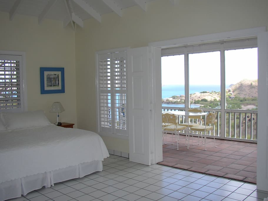 The king size bed and view through the screend in porch to the ocean