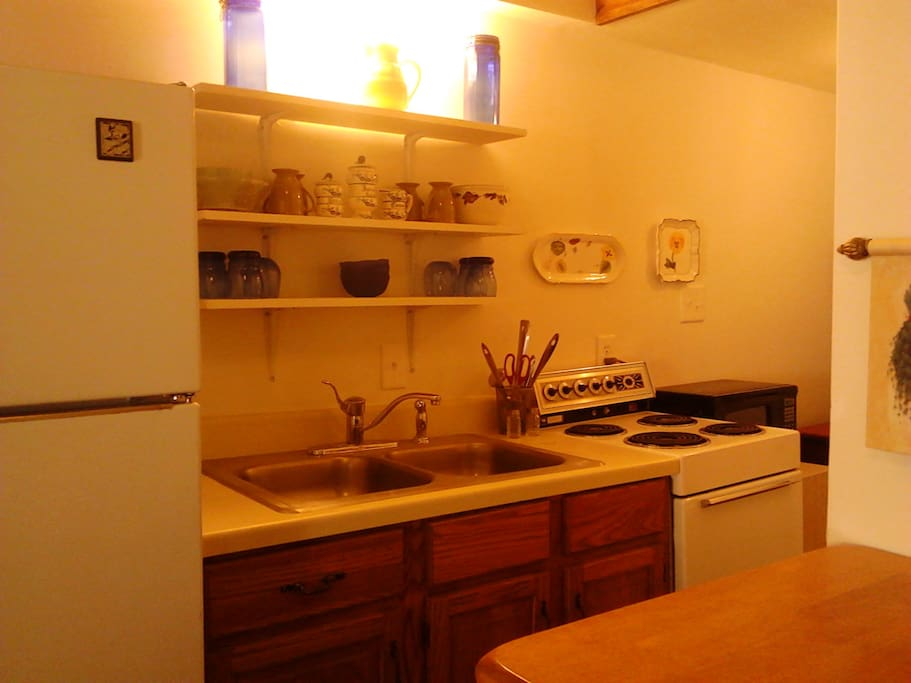 More detail of cooking area with coffee maker on counter and drawers across from sink. Microwave beside stove.