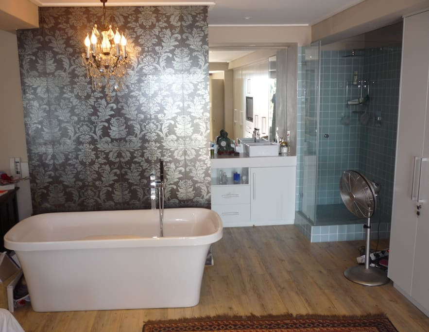 Open plan bathroom with a private concealed toilet.