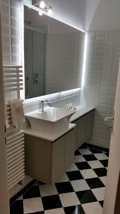 Bathroom with large mirror with led lights