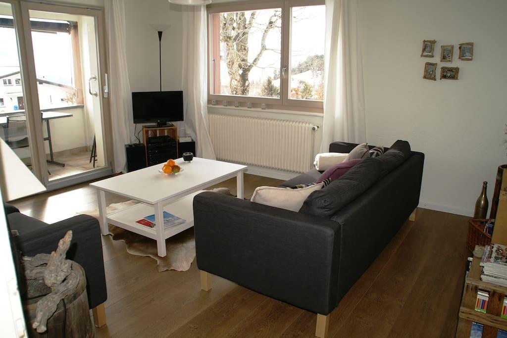 Sonniges Wohnzimmer mit gedeckter Veranda, TV, HiFi, W-Lan