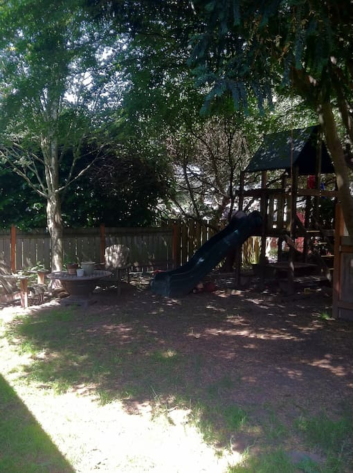 Fenced back yard with play structure for kiddos, dog.  Lots of shade