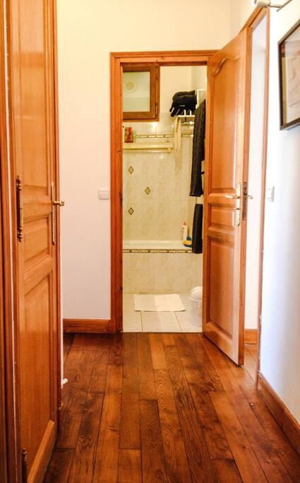 Un couloir qui dessert la cuisine, les toilettes et la chambre sur la gauche, la salle de bain au fond et le salon-salle à manger à droite