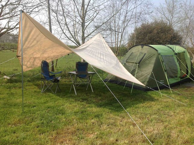 A large  fully equipped 4 birth tent in a field.