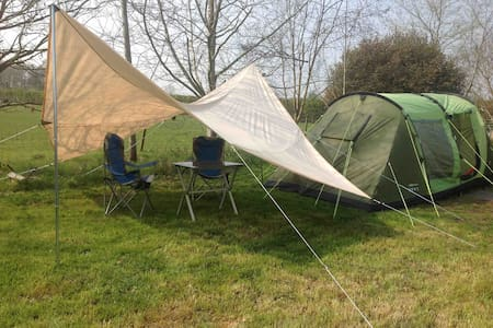 A fully equipped family tent pitched in a meadow.