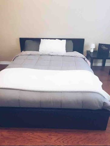 The second bedroom has a comfortable queen sized bed with soft bedding and a bedside table.